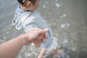 海で手をつなぐ親子