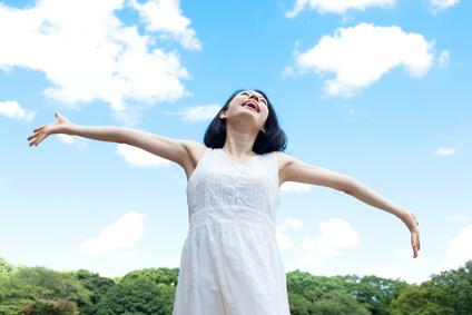 青空に手を広げる女性